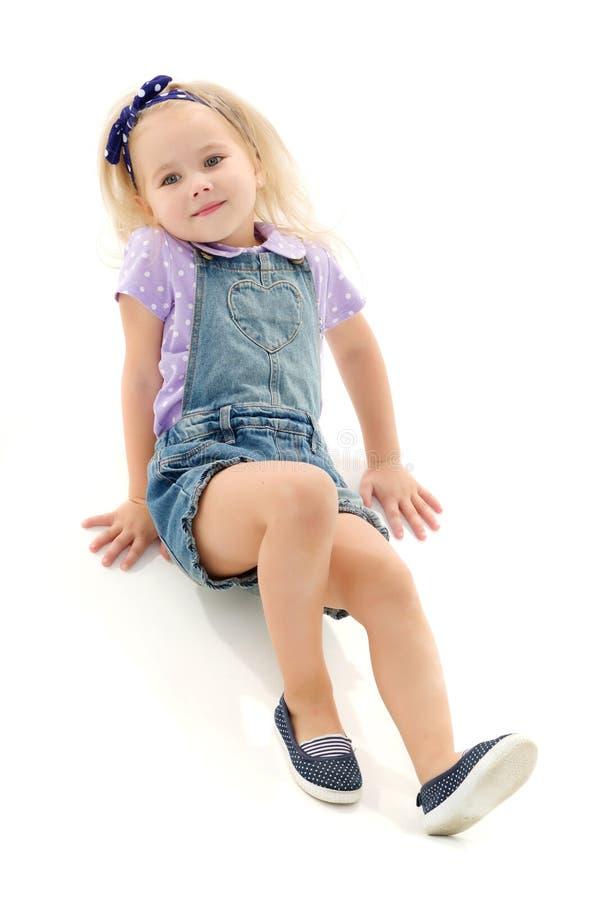 La petite fille se trouve sur le plancher photographie stock