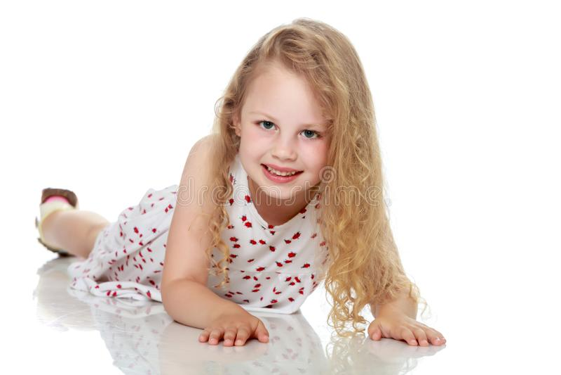 La petite fille se trouve sur le plancher images stock
