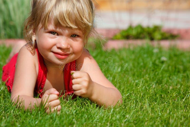La petite fille se trouve sur une pelouse image stock