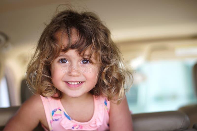 La petite fille semble heureuse dans la voiture photographie stock libre de droits