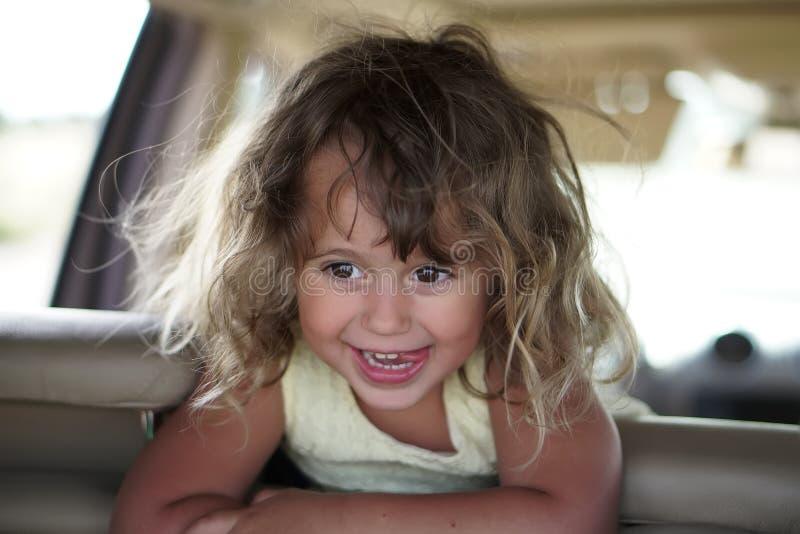 La petite fille semble heureuse dans la voiture photos stock