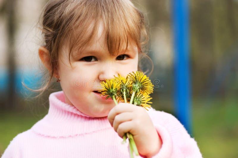 La petite fille sent des fleurs photographie stock libre de droits