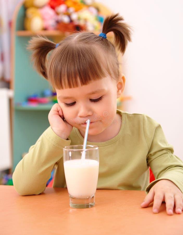 La petite fille sombre boit du lait image stock