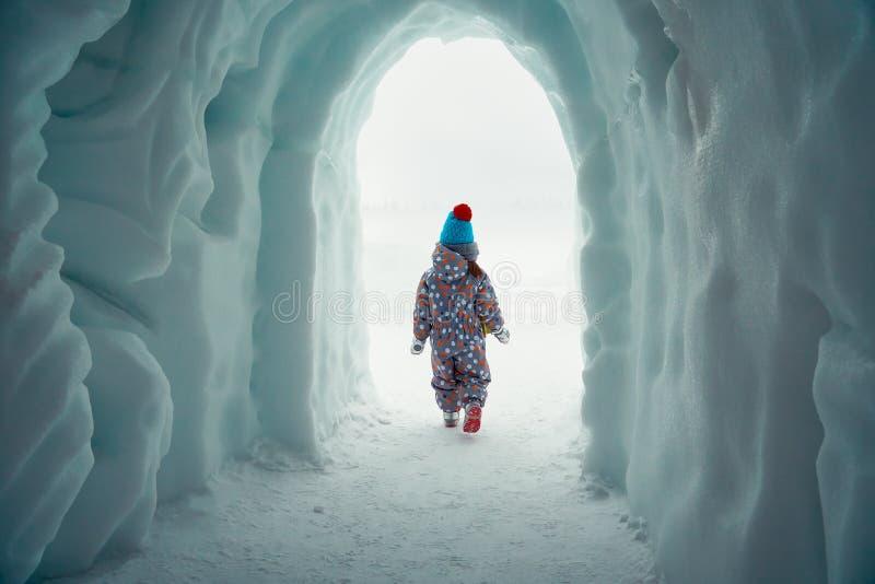 La petite fille sort d'une caverne de glace en parc d'hiver photographie stock libre de droits