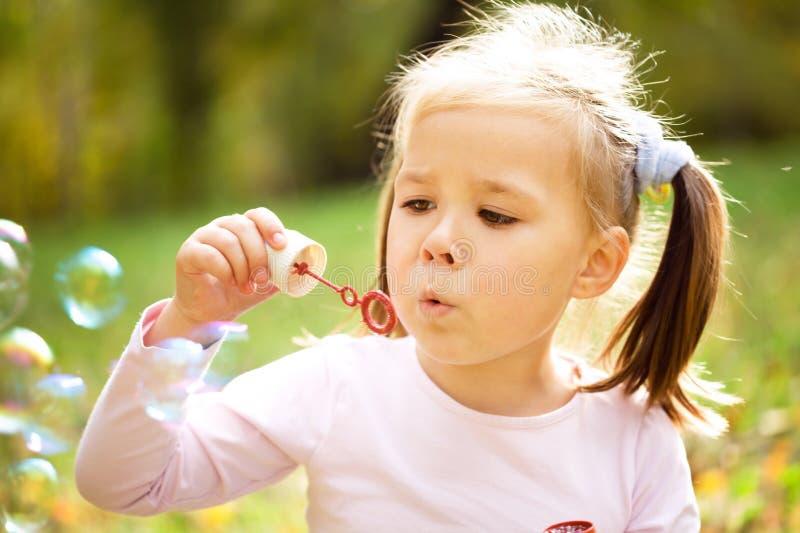 La petite fille souffle des bulles de savon photographie stock