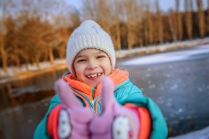 La petite fille soulève des pouces et rire photographie stock libre de droits