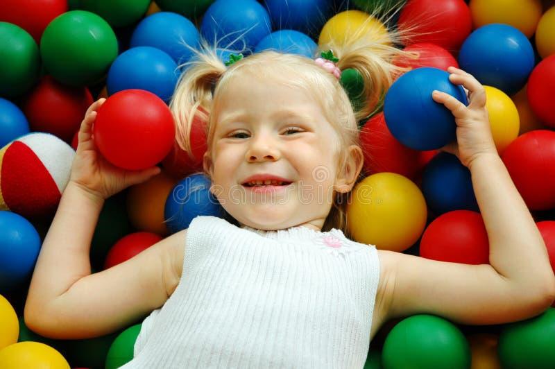 La petite fille sur des billes de couleur photos stock