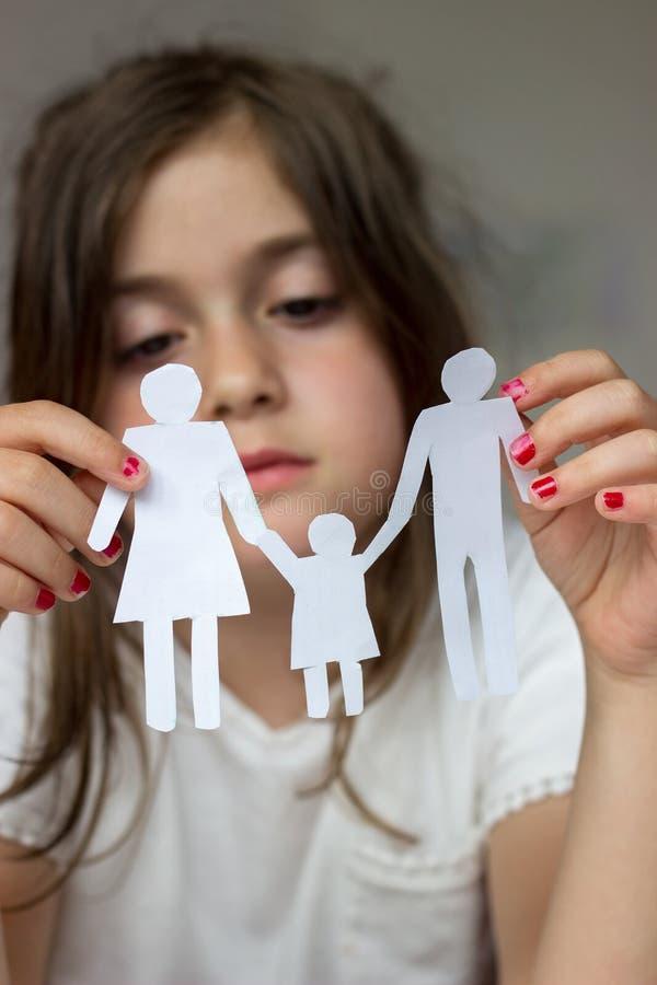 La petite fille tient la famille à chaînes de papier ; famille cassée ou divorce c photos stock