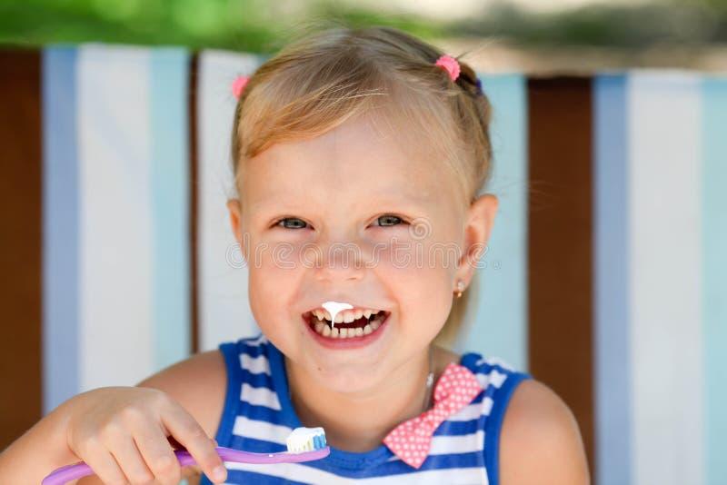 La petite fille tient une brosse à dents photos stock
