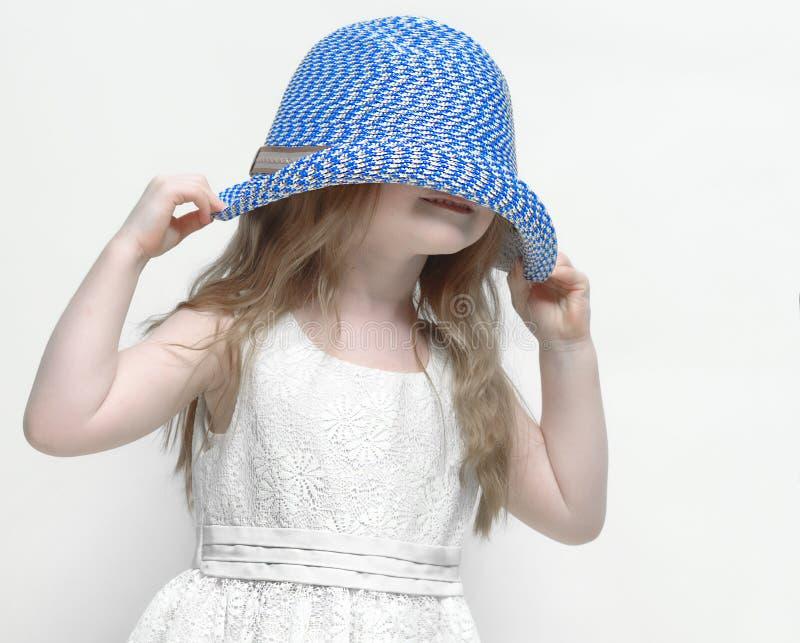 La petite fille tire son chapeau vers le bas au-dessus de sa tête photo libre de droits