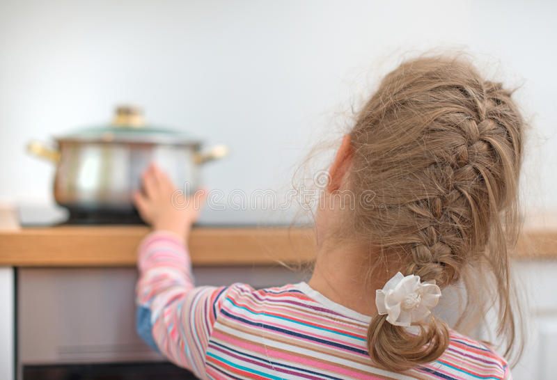 La petite fille touche la casserole chaude sur le fourneau photo libre de droits