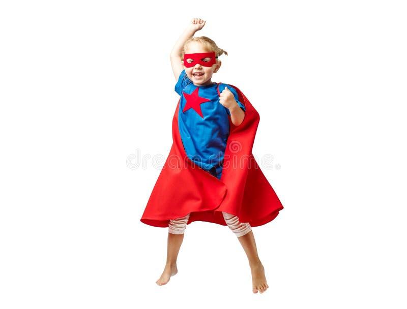 La petite fille très enthousiaste s'est habillée comme sauter de super héros d'isolement sur le fond blanc photos stock