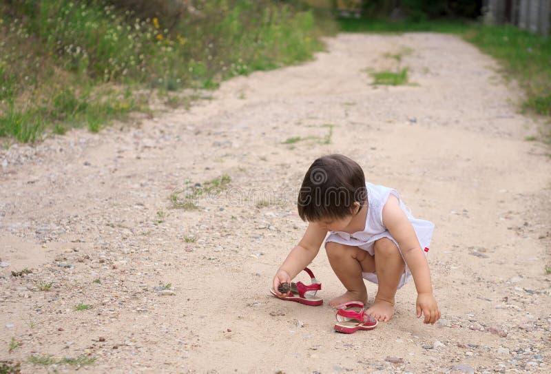 La petite fille a trouvé un cône de pin sur la route photo libre de droits