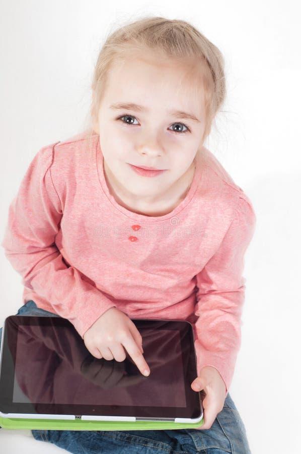 La petite fille utilise une tablette images libres de droits
