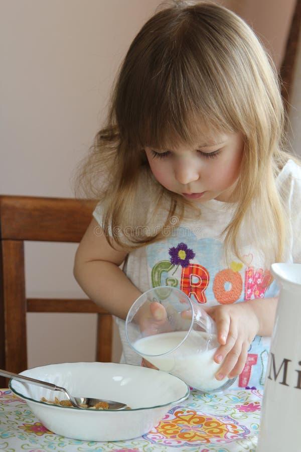 La petite fille verse le lait photo stock
