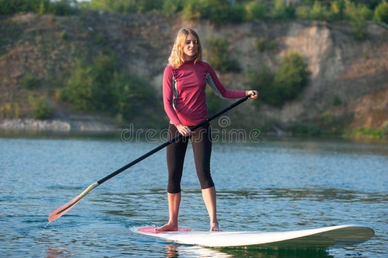 La PETITE GORGÉE tiennent la femme de panneau de palette paddleboarding image libre de droits