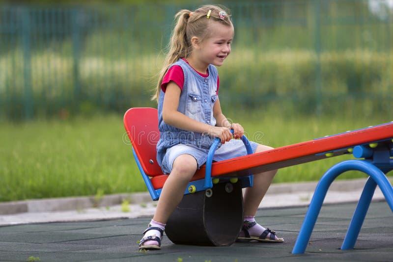 La petite jeune fille blonde mignonne d'enfant s'assied sur l'oscillation de bascule sur chaud photos stock