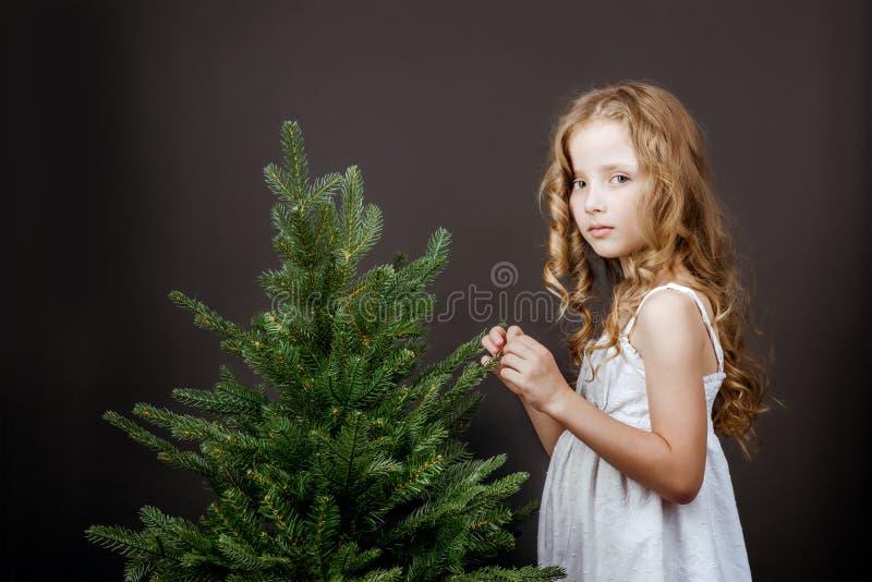 La petite jolie fille intelligente se tient près du concept d'arbre images stock