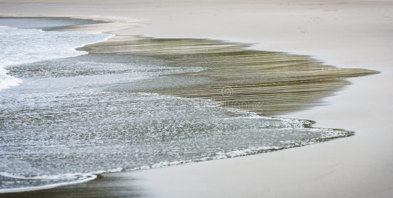 La petite mer d'océan ondule sur la plage sablonneuse par temps calme images stock