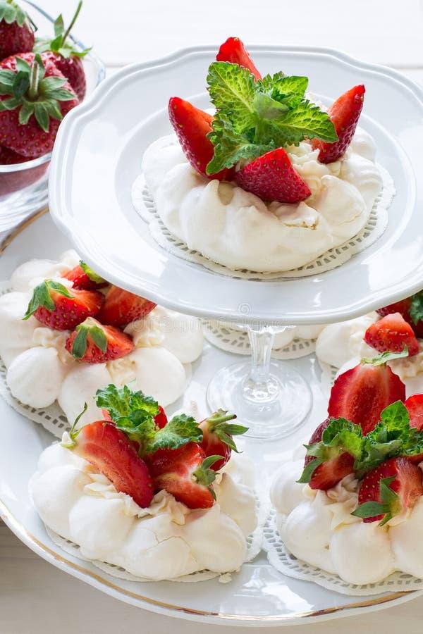 La petite meringue faite maison de vacherin de fraise durcit avec de la crème de mascarpone et les feuilles en bon état fraîches photographie stock libre de droits