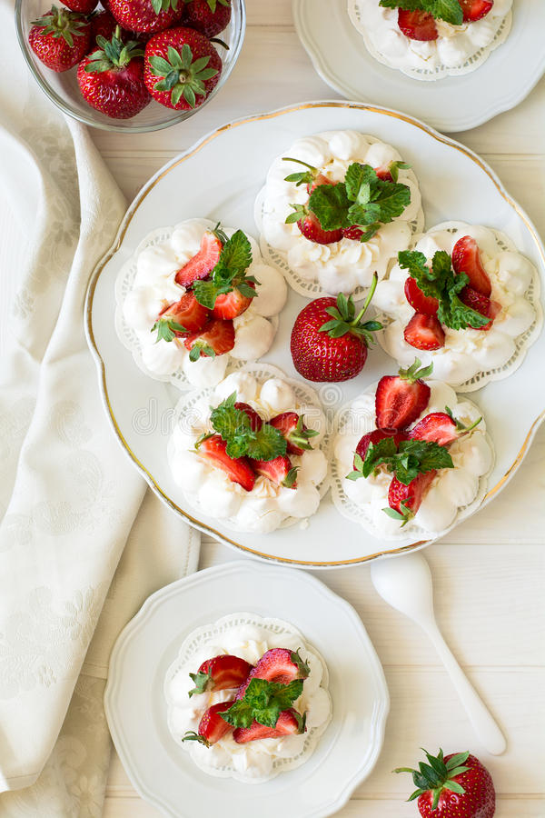 La petite meringue faite maison de vacherin de fraise durcit avec de la crème de mascarpone et les feuilles en bon état fraîches photo stock