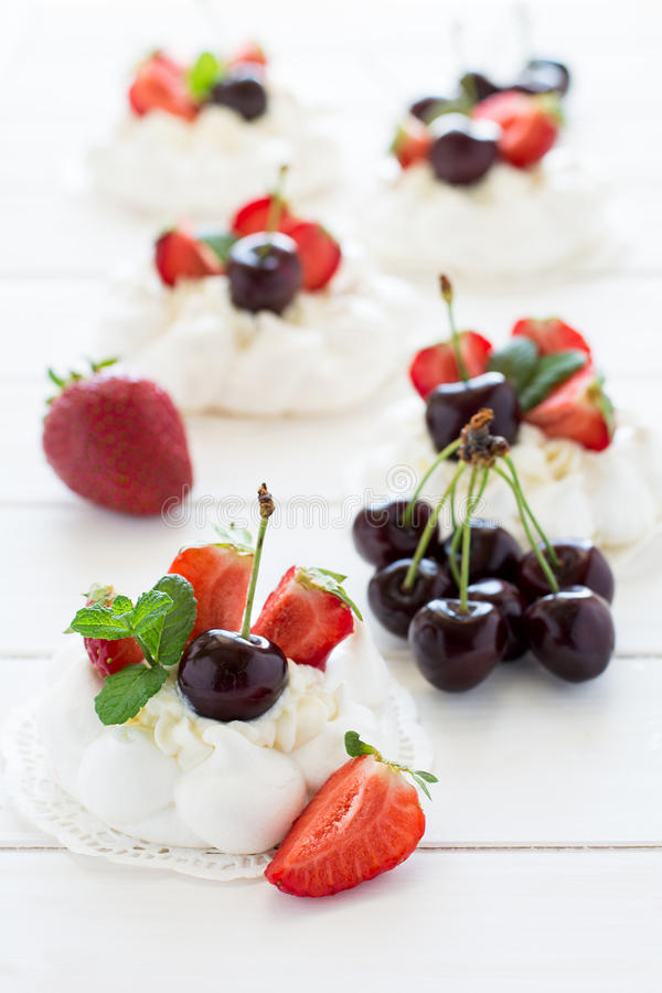 La petite meringue faite maison de vacherin durcit avec de la crème de mascarpone, des fraises, des cerises et des feuilles en bo images libres de droits