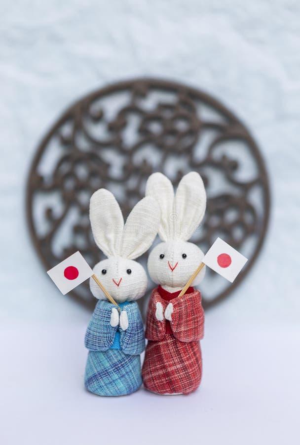 La petite poupée mignonne de lapin du tissu deux dans le beau Japonais traditionnel habillent tenir le drapeau du Japon images libres de droits
