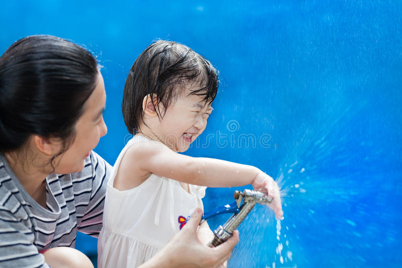 La petites fille et mère asiatiques jouent avec le tuyau de l'eau images libres de droits