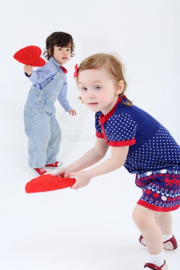 La petits beaux fille et garçon tiennent et tiennent les coeurs rouges photo stock