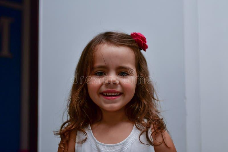 La peu de fille de sourires avec une fleur dans ses cheveux photo libre de droits