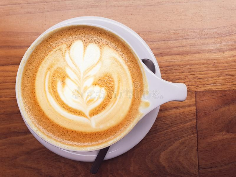 La photo aérienne d'un cappuccino fraîchement brassé avec une décoration gentille sur le dessus s'est reposée sur un fond en bois photos libres de droits