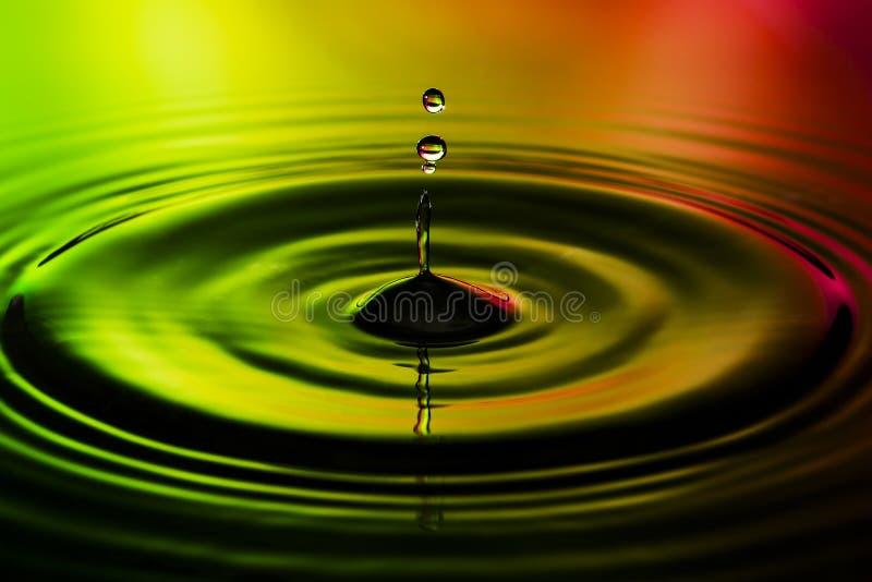 La photo abstraite de l'eau se laisse tomber sur le fond rouge gentil de vert jaune Photo gentille de texture et de conception photographie stock
