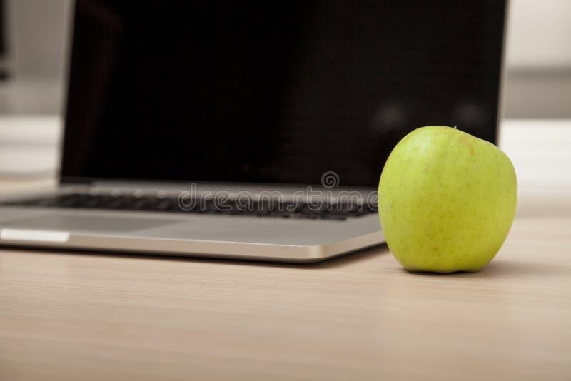 La photo conceptuelle, une pomme verte sur un ordinateur portable comme symbole de savent photo libre de droits