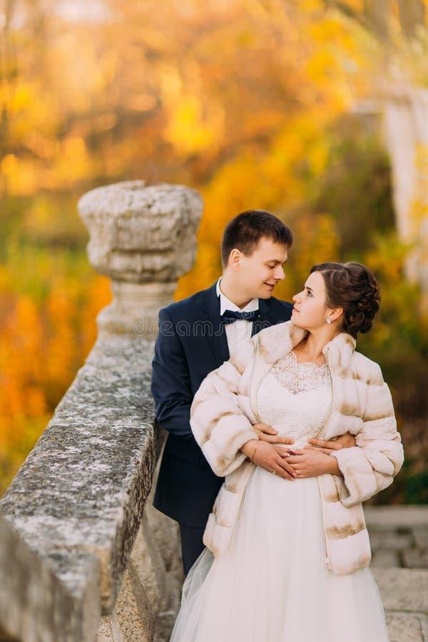 La photo d'autunm du marié étreignant le dos de jeune mariée tout en se tenant sur les escaliers gothiques au fond du photographie stock