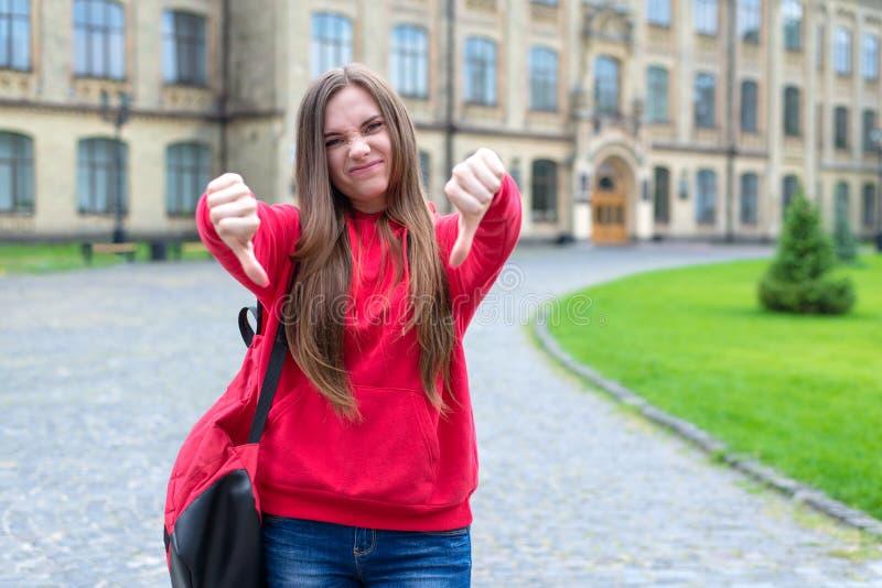 La photo d'indifférent n'aiment pas obtenir la connaissance et aller au doigt d'apparence d'adolescent de lycée en bas du symbole images libres de droits