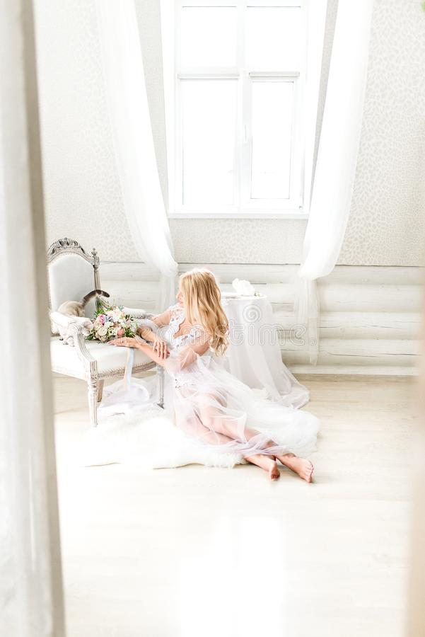 La photo d'une jeune jeune mariée dans un blanc a allumé l'intérieur photos stock