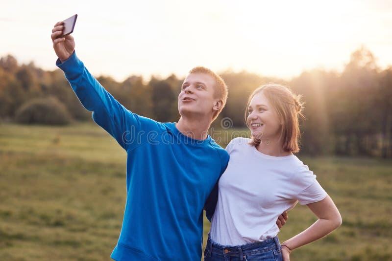 La photo de beaux couples joyeux se tiennent étroitement entre eux, regardent franchement dans l'écran du téléphone intelligent,  photographie stock