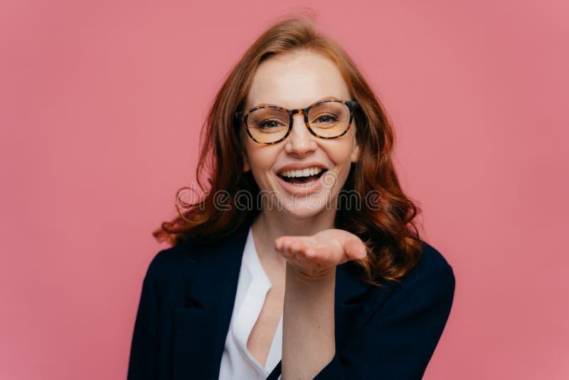La photo de la belle femme d'une chevelure rouge étire la paume au-dessus de la bouche, envoie le baiser d'air à la personne aimé image libre de droits