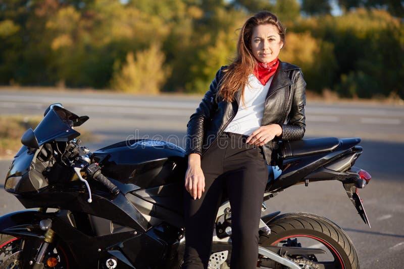 La photo de la femme assurée habillée dans la veste en cuir, pantalons noirs, se penche sur la motocyclette, a l'expression réflé image stock