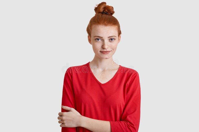La photo de la femme attirante avec les cheveux rouges, garde remettent le coffre, porte les vêtements sport, a la peau couverte  images stock