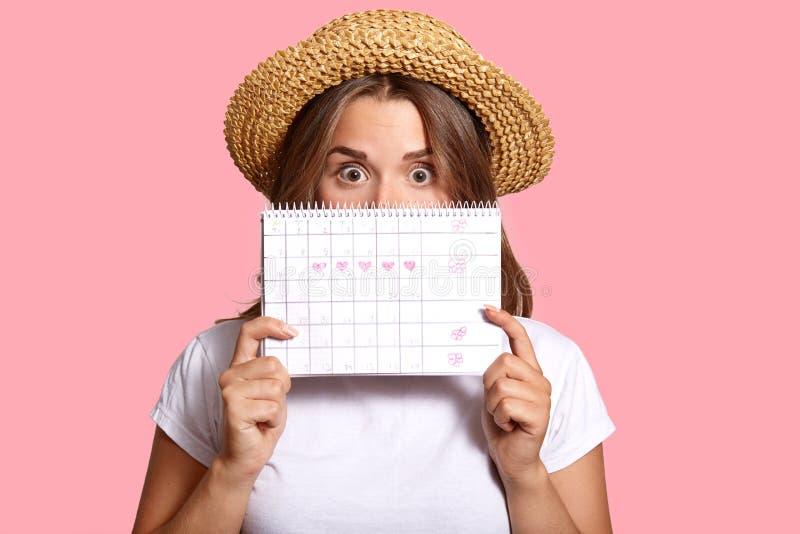 La photo de la femme d'une chevelure foncée étonnée se cache derrière le calendrier de périodes, utilise le T-shirt occasionnel e images stock