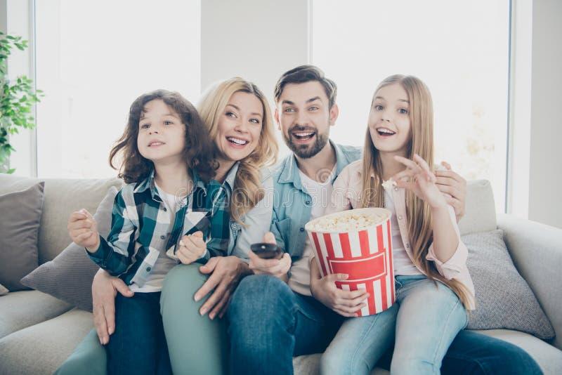 La photo de grands membres de la famille quatre excités en observant l'exposition de TV reposer le divan mangent du maïs éclaté s image stock