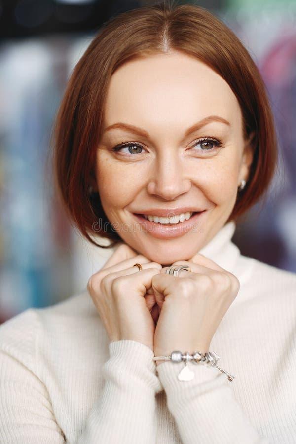 La photo de la jeune femelle attirante avec les cheveux droits bruns, regarde heureusement loin, habillé dans des vêtements blanc photographie stock libre de droits
