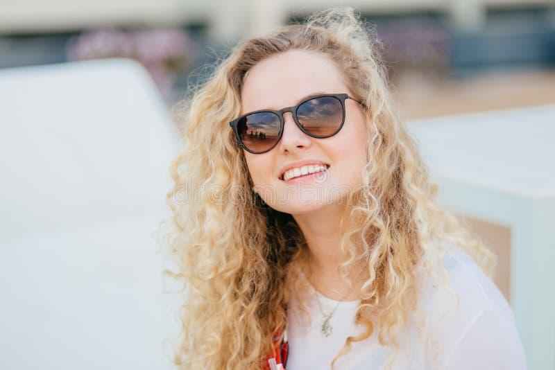 La photo de la jeune femelle attirante a les cheveux bouclés légers, porte les nuances à la mode, a le sourire toothy, montre les photos stock