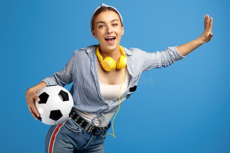 La photo de la jeune femme adorable avec le penny ou la planche à roulettes jaune, le ballon de football et les écouteurs dansent photos stock