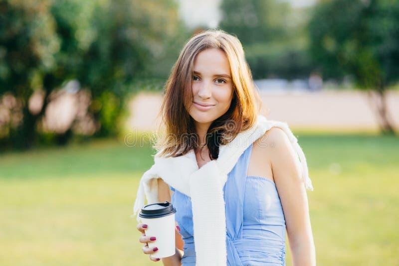La photo de la jeune femme agréable à regarder de brune avec l'aspect agréable, passe le week-end en air ouvert, a la balade à tr images libres de droits