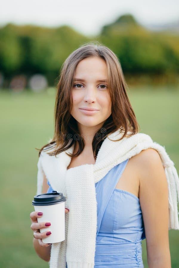 La photo de la jeune femme caucasienne attirante avec les cheveux foncés, café de boissons, préparé dans l'équipement occasionnel photographie stock