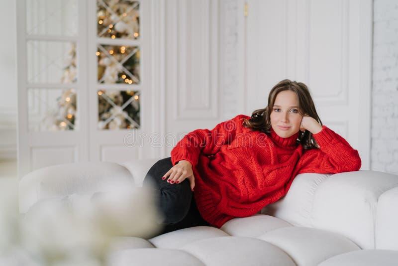 La photo de la jeune femme décontractée s'est habillée dans des vêtements tricotés chauds, mensonges sur le sofa confortable, app photos libres de droits