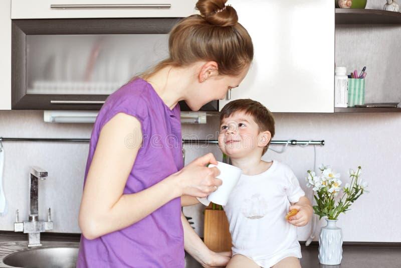 La photo de la jeune femme dans les vêtements décontractés se tient contre l'intérieur de cuisine, regarde son fils adorable avec photographie stock