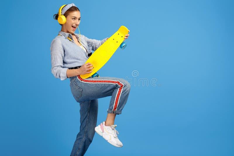 La photo de la jeune femme gaie avec les écouteurs jaunes jouent la guitare imaginaire avec le penny ou la planche à roulettes au image libre de droits